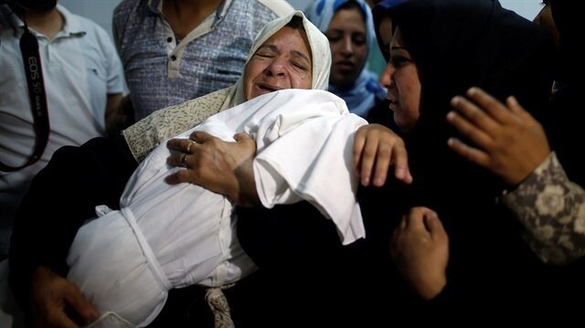 A relative mourns as she carries the body of 8-month-old Palestinian infant Laila al-Ghandour, who died after inhaling tear gas during a protest against the U.S. embassy move to Jerusalem, at the Israel-Gaza border, during her funeral in Gaza City May 15, 2018.