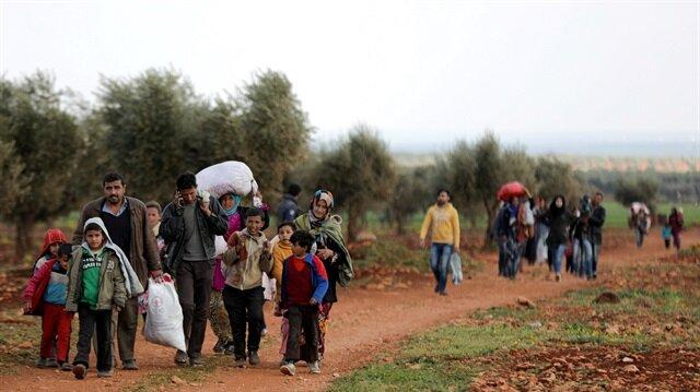 Internally displaced people walk with their belongings