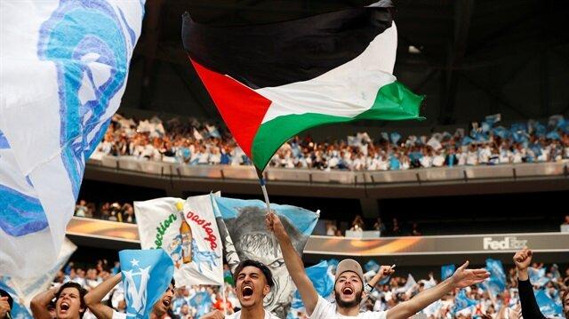 UEFA Avrupa Ligi finalinde Atletico Madrid ile karşılaşacak Marsilya'da taraftarlar İsrail tarafından kalleşçe saldırıya uğrayan Filistinlilere destek olmak için tribünde Filistin bayrağı açtı.