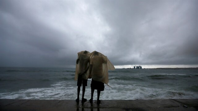 Two men use a plastic sheet to protect themselves from heavy monsoon rain as they stand by the sea in Colombo, Sri Lanka May 17, 2018.