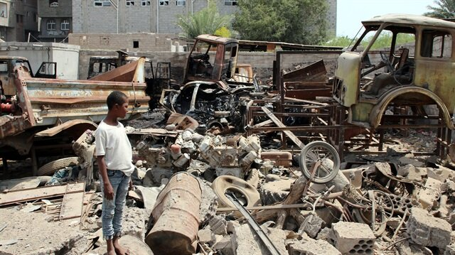 People inspect the damages after a car bomb ripped through a military kitchen in Aden