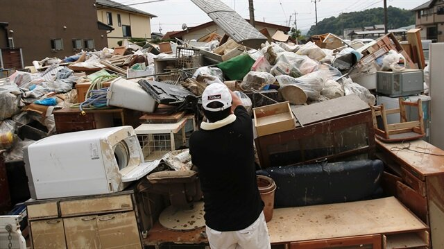 A local resident tries to clear debris at a flood affected area in Mabi town in Kurashiki, Okayama Prefecture, Japan.