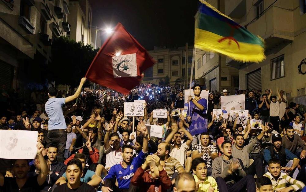 Berberi kimliği, Mağrib bölgesinde çok belirgin. Fas'ın başkenti Rabat'ta düzenlenen bir gösteride, Berberi bayrağı (sağda) açan gençler.