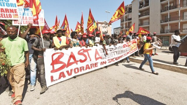 Göstericiler, yaz aylarında tarlalarda çalışırken güneşten korunmak için taktıkları kırmızı şapkalarla yürüyüş yaptı.