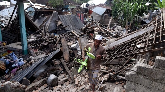 A man carries a small bicycle through the ruins of houses damaged by an earthquake in West Lombok, Indonesia