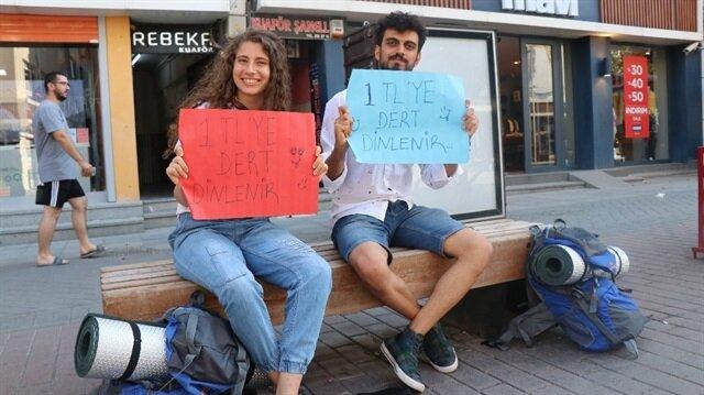"""Malatya'da Halkla İlişkiler ve Tanıtım bölümünde eğitim gören son sınıf öğrencileri otostop çekerek ziyaret ettikleri şehirlerin en işlek caddelerinde """"1 liraya dert dinlenir"""" yazılı pankartla bekliyor."""