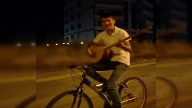 Bisikletle seyir halindeyken bağlama çalan adam
