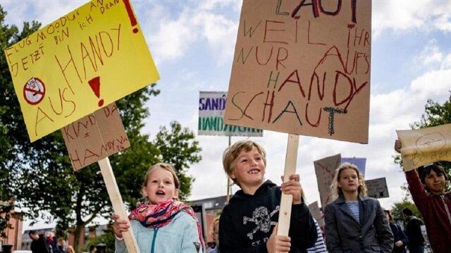 Almanya'da bir çocuk tarafından organize edilen gösteride, anne-babalar telefonla çok oynadıkları için eleştirildiler.