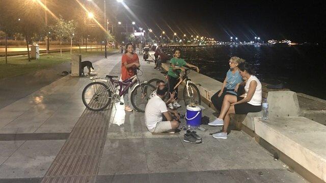 İzmir'de kenti saran kokuya tepki gösteren vatandaşlar, çözümü ev yerine sahilde oturmakta arıyor.