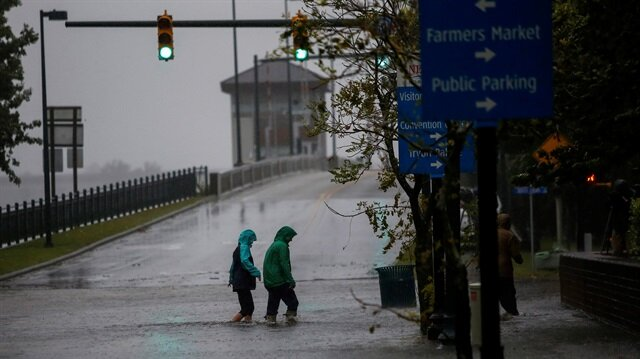 People walk on a local street as water from Neuse River starts flooding houses upon Hurricane Florence coming ashore in New Bern, North Carolina, U.S., September 13, 2018.