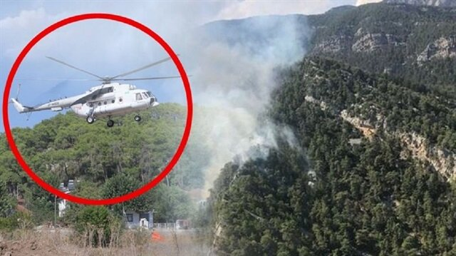 Antalya'da yangına müdahale eden helikopter pilotu yakıt ikmali için köye indi.