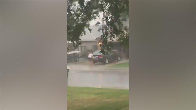 Fırtınalı havada araç yıkayan kadın
