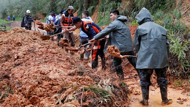 Police officers and fire marshals clear debris and fallen trees caused by a landslide