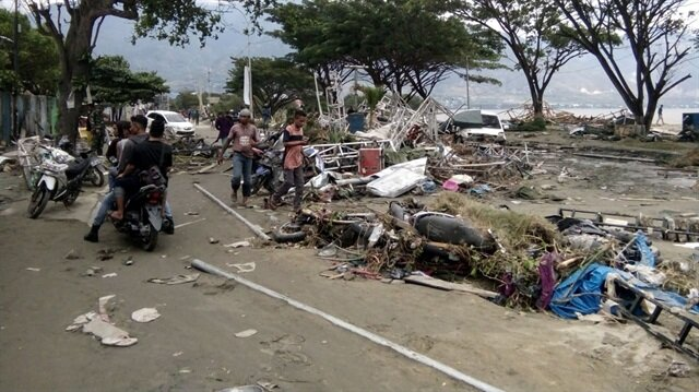 Resident checks dead bodies to find their family at a street after tsunami hit in Palu, Indonesia September 29, 2018.