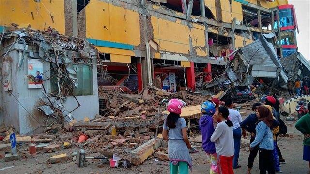 Residents stand in front of a damaged shopping mall after an earthquake hit Palu, Sulawesi Island, Indonesia September 29, 2018.
