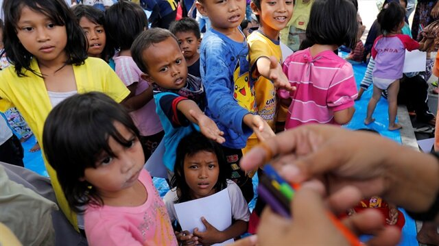 Children reach for coloured pencils while attending a class at a camp for displaced people following the earthquake and tsunami in Palu, Central Sulawesi, Indonesia October 8, 2018