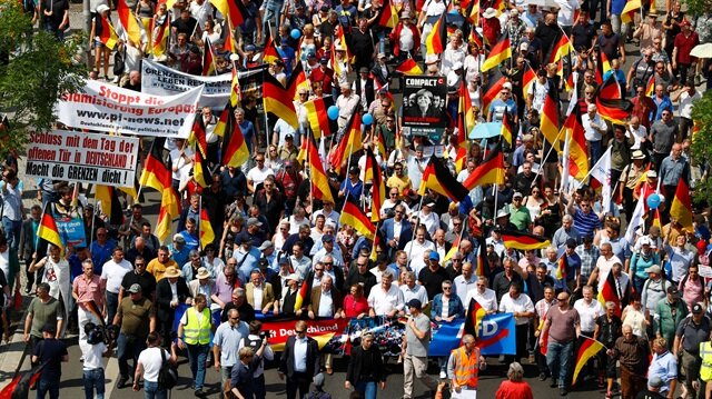 Supporters of the Anti-immigration party Alternative for Germany (AfD) hold German flags during a protest in Berlin, Germany, May 27, 2018