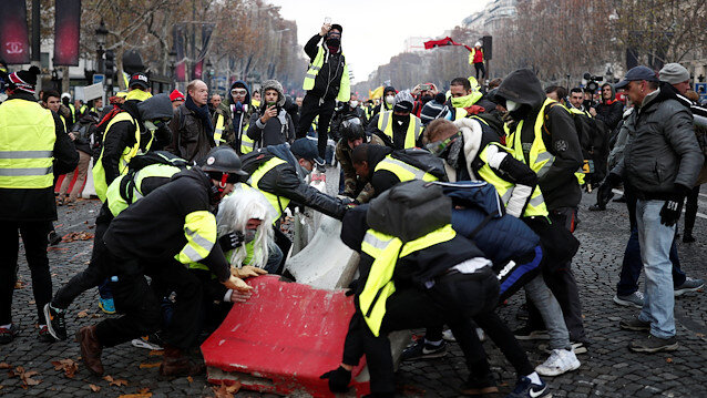 Protesters wearing yellow vest, a symbol of a French drivers' protest against higher fuel prices, build a barricade during clashes on the Champs-Elysees in Paris, France, November 24, 2018.