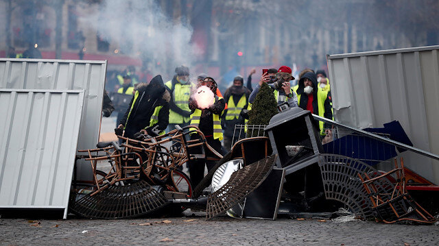 A protester wearing yellow vest, a symbol of a French drivers' protest against higher fuel prices, fires a flare during clashes on the Champs-Elysees in Paris