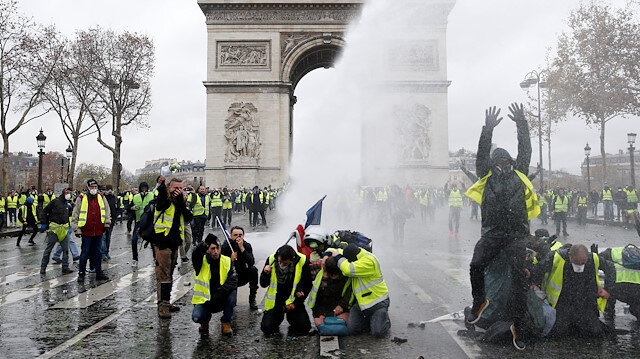 Protesters wearing yellow vests, a symbol of a French drivers' protest against higher diesel taxes, stand up in front of a police water canon at the Place de l'Etoile near the Arc de Triomphe in Paris, France