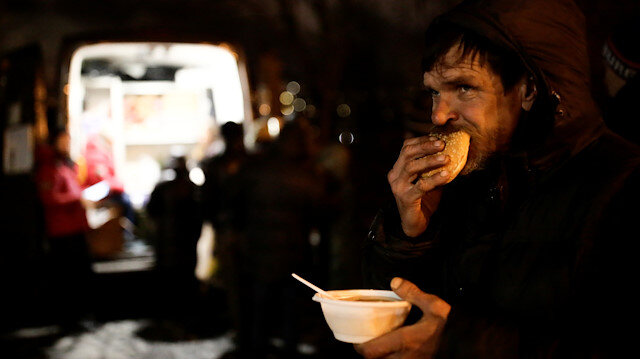 A man eats soup and bread near a van of 'Nochlezhka' charity organization as volunteers distribute meals for homeless people in St. Petersburg, Russia December 5, 2018