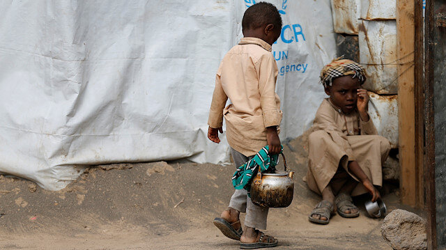 A boy holds a kettle as he walks outside his family's hut at a camp for people displaced by conflict