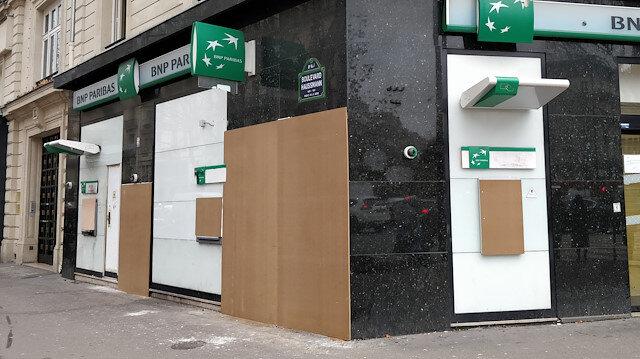 Fransa'nın başkenti Paris'te, önceki gösterilerde camları zarar gören bazı banka şubelerinde önlem alındığı görüldü. (Fotoğraf: AA)
