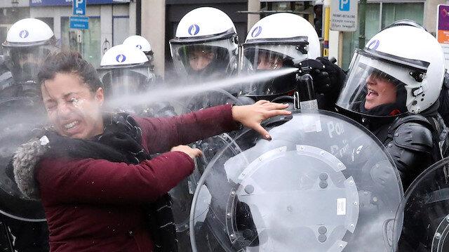 Brüksel'de bir göstericiye tazyikli su sıkan polis.