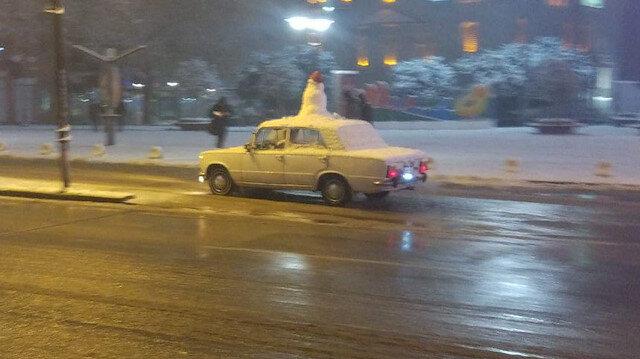 Aracının üzerine kardan adam yapıp sokak sokak gezdi