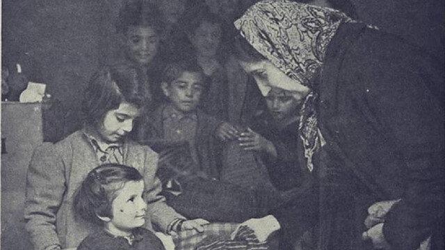 Suriyeli kadınların Yunan çocuklara kıyafet dağıttığı fotoğraf