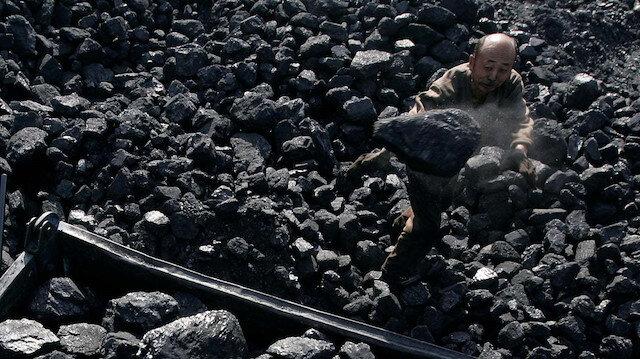 Çinli bir adam, 19 madencinin öldüğü Shaanxi bölgesindeki bir arabaya kömür yüklüyor. Fotoğraf: Reuters