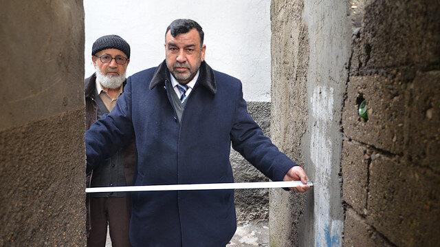 Genişliği 90 santim olan sokakta metreyle ölçüm yapan vatandaşlar.