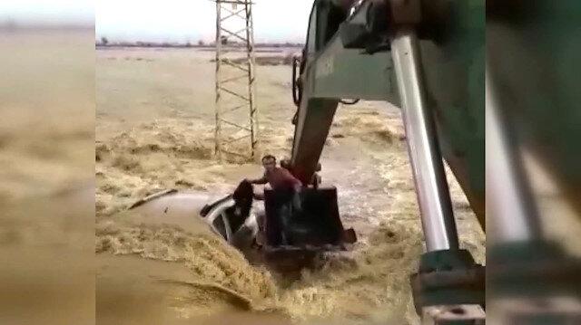 Sel sularına gömülen araçtan kepçeyle kurtarıldılar