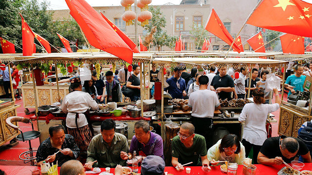People eat under Chinese national flags in the Old City in Kashgar in Xinjiang Uighur Autonomous Region, China September 6, 2018. Picture taken September 6, 2018. To match Special Report MUSLIMS-CAMPS/CHINA REUTERS/Thomas Peter