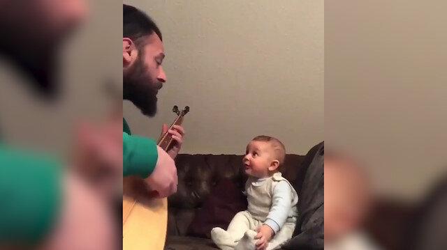 Babasından Bil oğlum türküsünü hayranlıkla dinleyen bebek