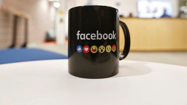 The Facebook logo and emoticons are seen on a coffee mug