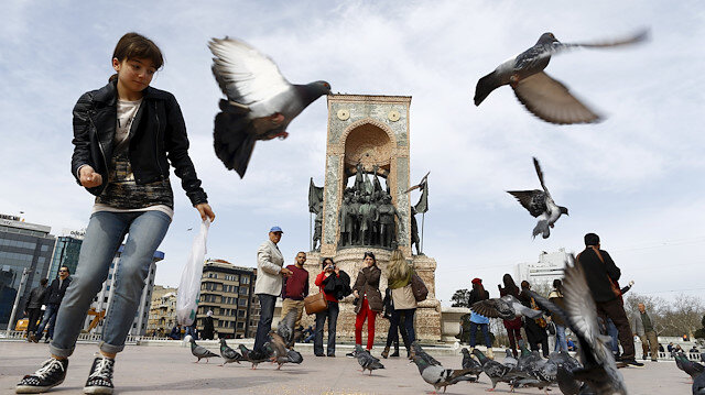 Local and foreign tourists stroll at Taksim square in central Istanbul, Turkey