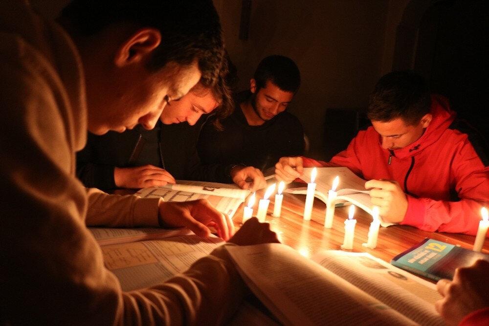 Eğitim hayatlarına devam eden genç futbolcular, mum ışığı altında ders çalışıyor.
