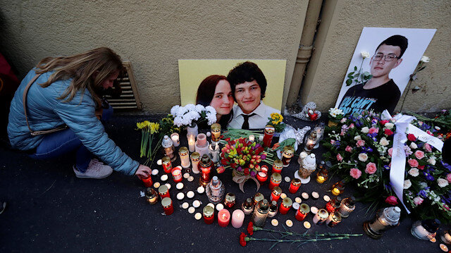A woman kneels by a memorial on the first anniversary of the murder of the investigative reporter Jan Kuciak and his fiancee Martina Kusnirova in Bratislava, Slovakia, February 21, 2019