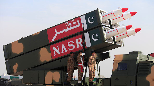 Pakistani military personnel stand beside short-range Surface to Surface Missile NASR