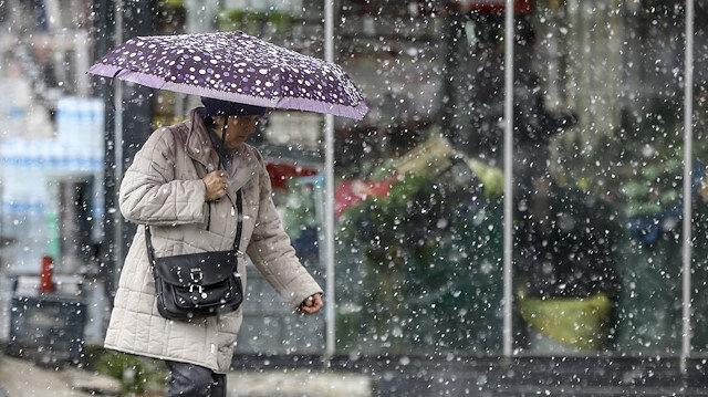Karla karışık yağmur altında yürüyen bir kadın.