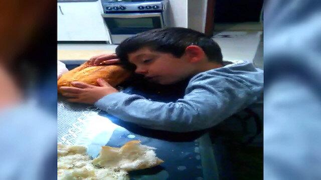 Sofrada ekmekle uyuklayan çocuk ilgi odağı oldu