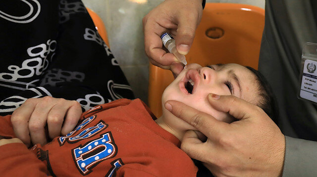 A boy receives polio vaccine drops by anti-polio vaccination workers