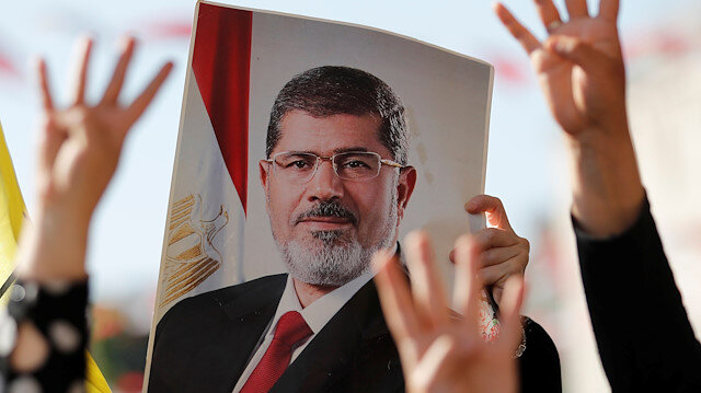 People flash Rabia signs as they hold a picture of former Egyptian president Mohamed Mursi during a symbolic funeral prayer at the courtyard of Fatih Mosque in Istanbul, Turkey, June 18, 2019. REUTERS/Murad Sezer NO RESALES.