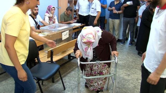 71 yaşındaki bir kadın yürüteç ile oy kullanmaya gelerek vatandaşlık görevini yerine getirdi.