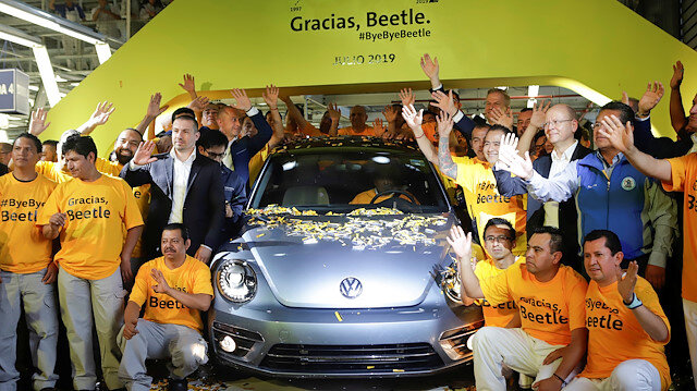 Employees pose for a picture next to a Volkswagen Beetle car during a ceremony marking the end of production of VW Beetle cars, at company's assembly plant in Puebla, Mexico, July 10, 2019