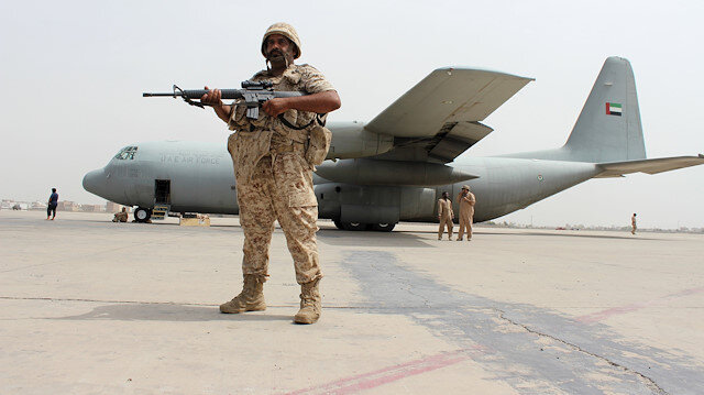 A soldier from the United Arab Emirates stands guard next to a UAE military plane at the airport