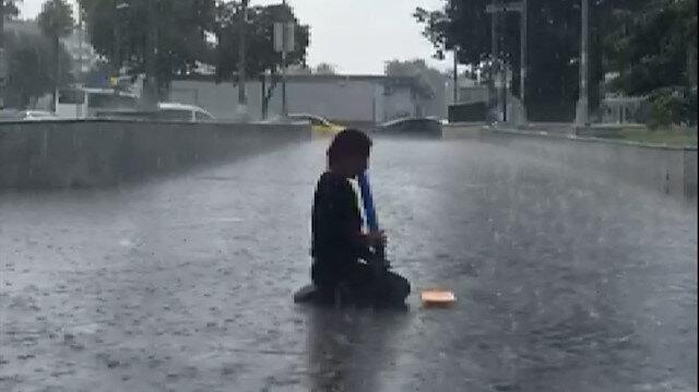 Sağanak yağış altında melodikasını çalmaya devam etti