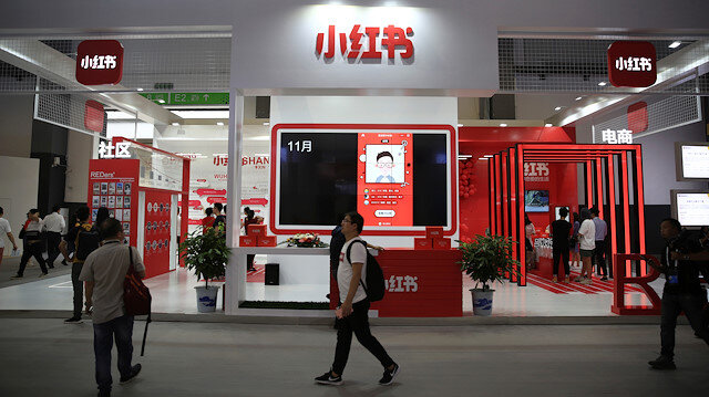 "File photo: A man walks past the booth of Chinese startup Xiaohongshu, which means ""little red book"" in Chinese, at the Big Data Expo in Guiyang, Guizhou province"