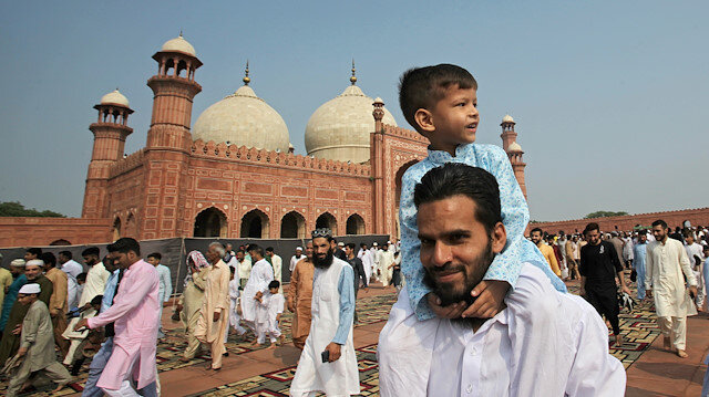 A boy sits on the shoulder of his father as they leave after attending the Eid al-Adha prayer at the Badshahi Mosque in Lahore, Pakistan August 12, 2019. REUTERS/Mohsin Raza